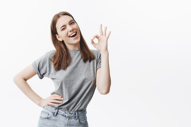 portrait-cheerful-beautiful-young-brunette-girl-with-medium-hair-lengths-casual-stylish-clothes-winking-with-satisfied-joyful-expression-showing-ok-gesture-with-hand_176420-10657